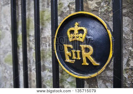 Queen Elizabeth II symbol on a gate at the Tower of London.