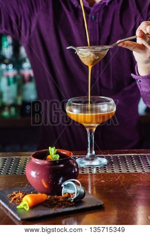 Barman pouring cocktail from shaker and serving it