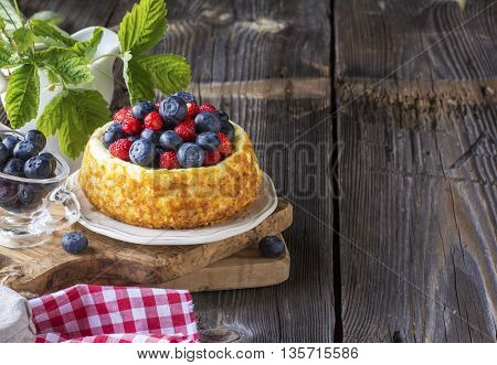 Lovely home fragrant delicate cheesecake with strawberry strawberries, juicy blueberries, served with liquid honey with floral honey comb on a simple wooden background.