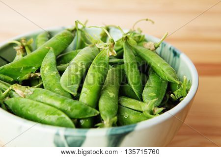 Green Peas In Pods Freshly Picked On Wood