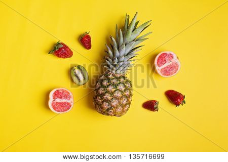 Top view of fresh fruits on yellow background. Overhead concept shot of pineapple, strawberries, sliced kiwi and grapefruit. No retouch, no filter.