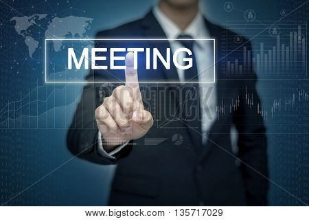 Businessman hand touching MEETING button on virtual screen