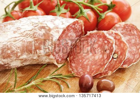 Rustic italian snack closeup - salami tomatoes herbs and olives