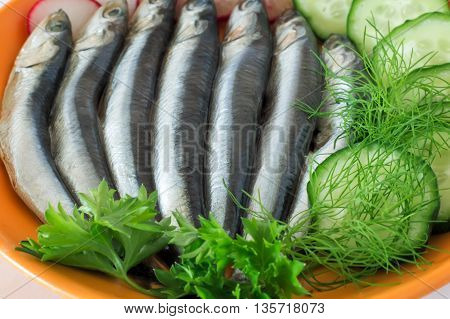 On the yellow plate are small salted fish anchovies next to the cucumbers with parsley dill. Presents closeup.