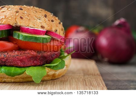 Veggie beet burger with lamb's lettuce, tomato, radish and cucumber on rustic wood