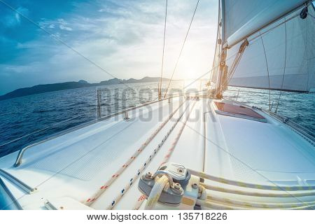 Sailing vessel moving in the open sea at sunset with mountains on the background