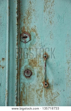 old rusty shabby metal green door with metal handle and door latch