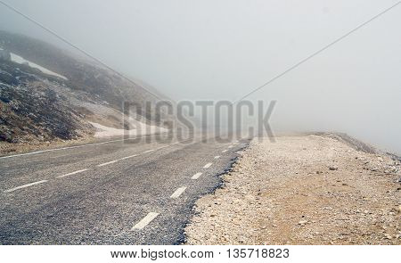 fog-shrouded mountain road in the alps by daylight
