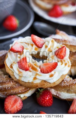 Cream Puff Rings Decorated With Fresh Strawberry And Caramel Sauce