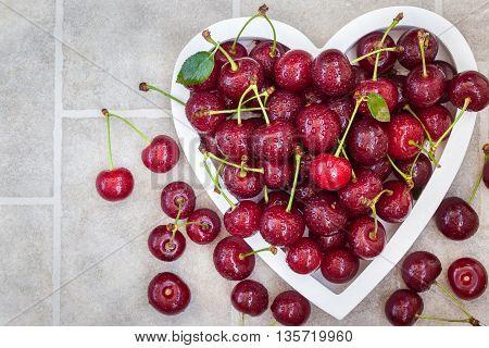 Fresh wet summer cherry in heart shaped bowl
