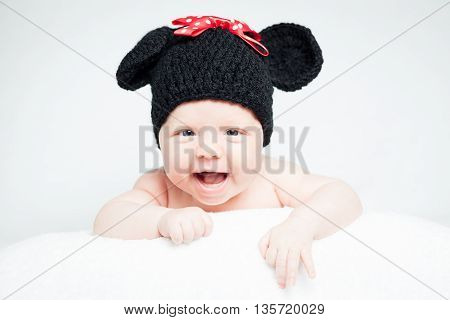 Newborn baby with hat on the head lying on blanket. Smiling cute newborn baby girl.