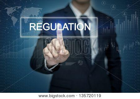 Businessman hand touching REGULATION button on virtual screen