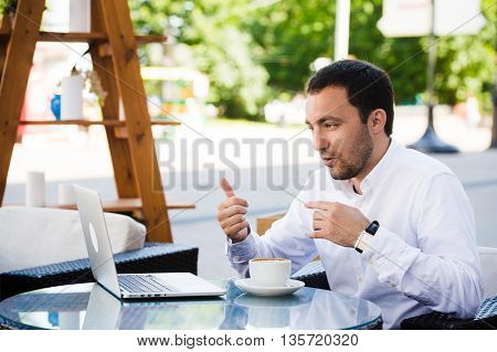 Closeup shot of young man smiling and using digital tablet at cafe. Guy is doing breakfast and making video call with laptop