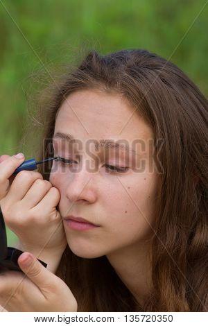 Blonde girl doing make-up, closeup photo. Eyeliner