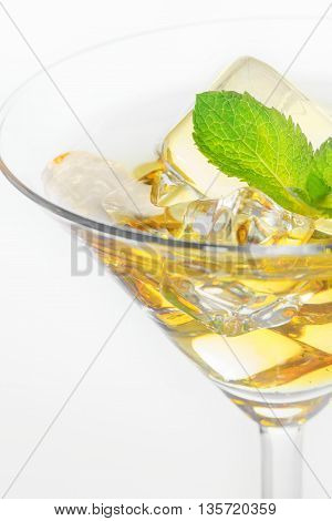 Martini glass with ice and mint on white background