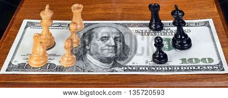 Chess pieces on American hundred dollar bill.