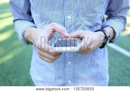 Business man holding and use white smartphone