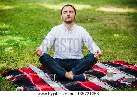 Man businessman meditating outdoors in lotus pose.