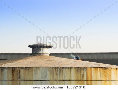 Lonely laber welding on rooftop of big tank
