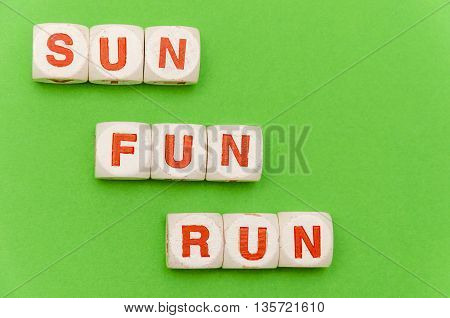 still life with dices and the word sun fun and run green background