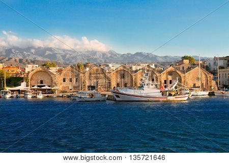 view of bay with historical houses and boats at sunny summer day in Chania, Crete, Greece