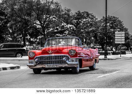 HAVANA, CUBA - JULY 05, 2015: HDR black white - Red american cabriolet classic car drives on the Malecon Promenade in Havana
