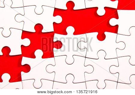 white jigsaw/puzzle wite some gaps over red background symbol of problem solving