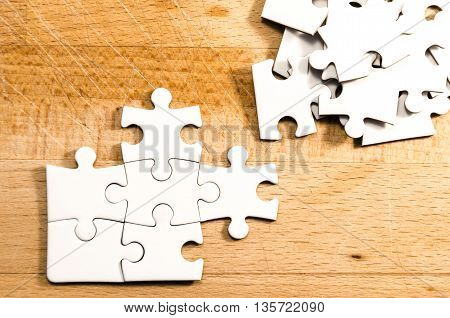 white jigsaw/puzzle unfinished over a wooden table background symbol of problem solving