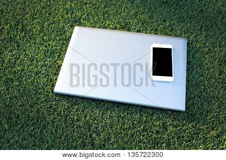 tablet and laptop on a artificial turf