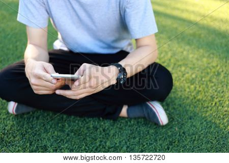 Man sitting with use smartphone on artificial turf