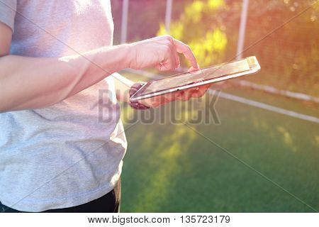 Hand holding with touch on tablet on green grass