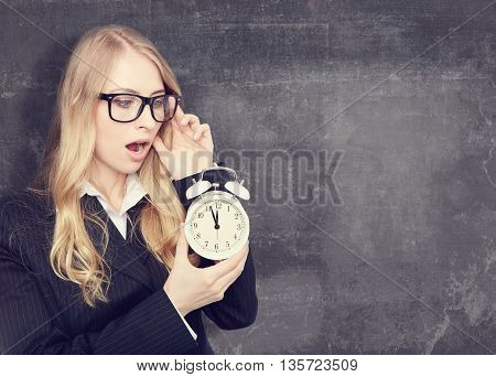 Woman holding with on office clock.chalkboard background