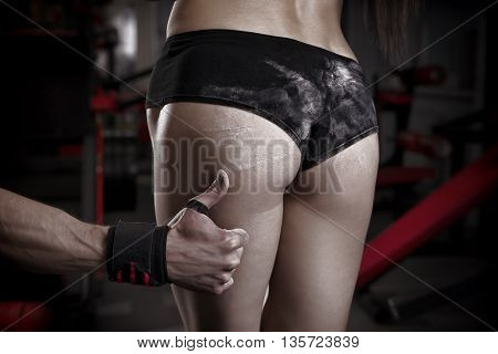Sexy fitness ass close-up. Perfect female muscular buttocks. Muscular woman posing in gym