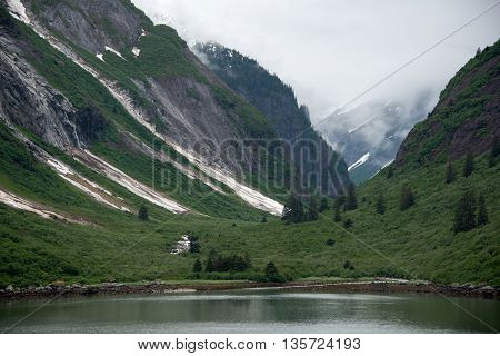 Landscape image of snowy mountains and mist-covered valley created by Alaskan glacier, with meadow and water in the foreground.
