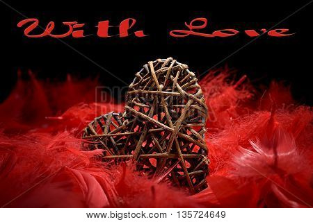 wooden heart in the midst of red feathers on a black background and with love written