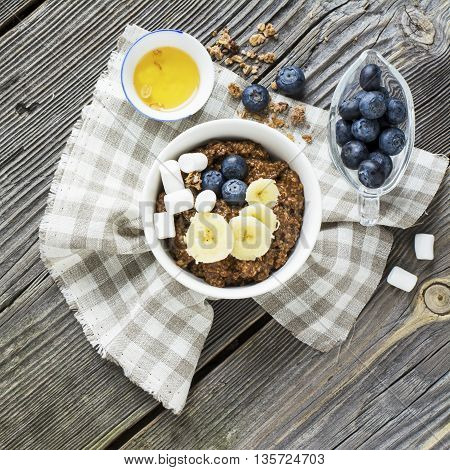 Healthy breakfast in the trend. Chocolate milk porridge of oat bran with banana, blueberries blueberry and marshmallow portions with honey on wooden gray background.