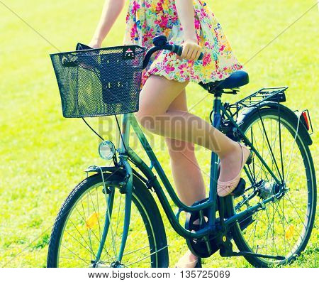 Young woman in short colorful dress with long hair rides a bicycle with basket and flowers tour summer city park. Toned photo