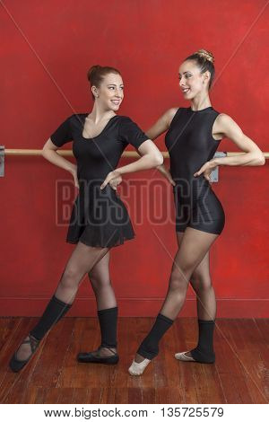 Ballerinas Smiling While Looking At Each Other In Studio