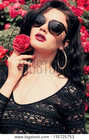 fashion outdoor photo of gorgeous sensual woman with dark hair and bright makeup, in elegant black lace dress posing beside roses at summer garden