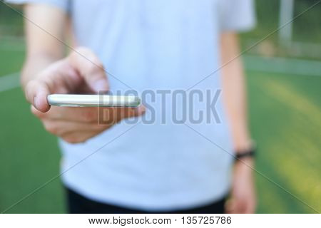 Man holding white smartphone on a background of green grass .