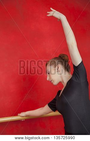 Female Ballet Dancer With Hand Raised At Barre