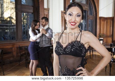 Woman With Hand On Hip Smiling While Dancers Doing Tango