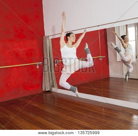 Ballerina Jumping While Performing In Dance Studio