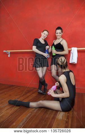 Happy Ballerinas Holding Water Bottles In Studio