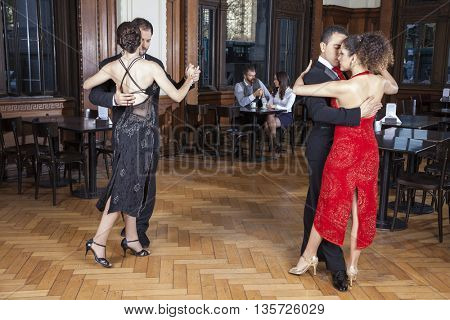 Dancers Performing Tango While Couple Dating In Restaurant