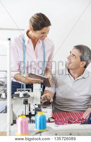 Smiling Tailors Using Digital Tablet In Factory