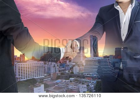 Double exposure of two businessman handshake and city