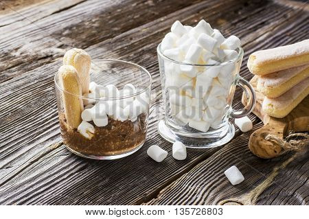 Chocolate Oatmeal with milk of oat bran is decorated with marshmallow and serve for the winter a cozy breakfast room with fir branches on a wooden gray background. Decorated cookies Savoiardi. selective focus