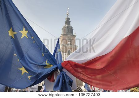 Polish and EU Flags Tied Together foreground Krakow Town Hall Tower in the background clear sky