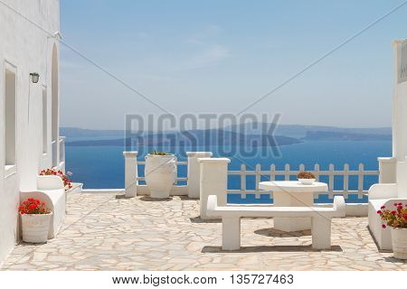 white bench against Aegan sea and volcano caldera, beautiful details of Santorini island, Greece